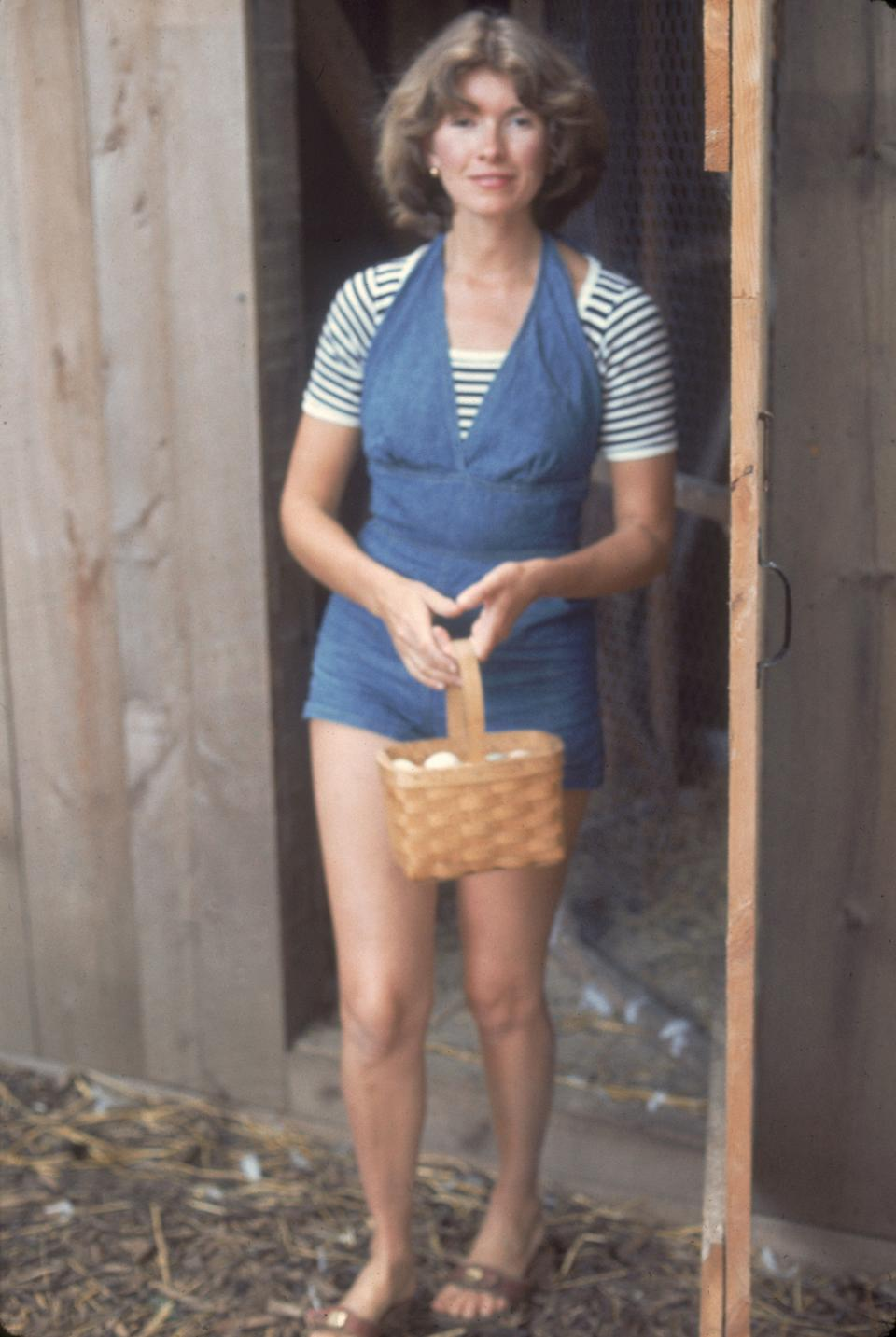 Stewart outside a chicken coop holding a basket of eggs in August 1976.