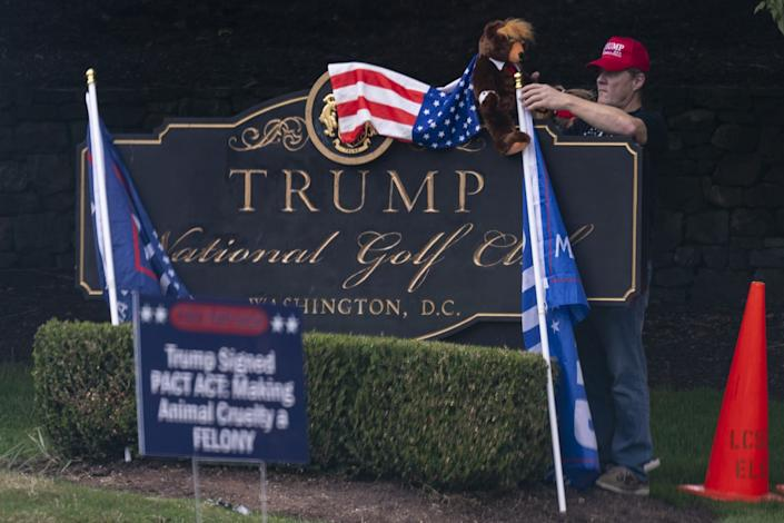 """A supporter of President Trump places a """"Trumpy Bear"""" atop the sign of Trump National Golf Club."""