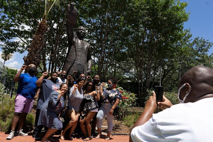 People pose in front of the statue of former Texas Representative Al Edwards
