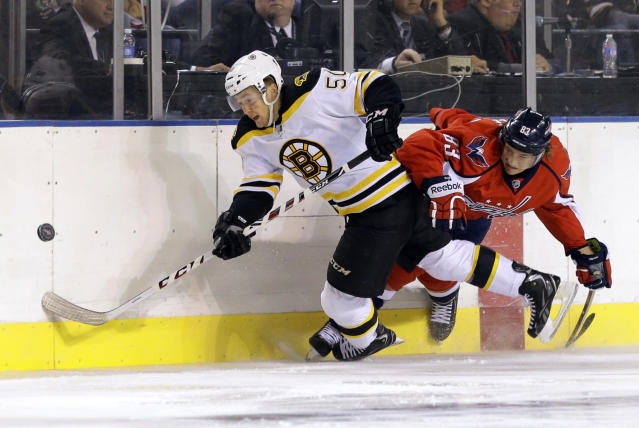 Boston Bruins center Jared Knight, left, tries to keep possession of the puck as Washington Capitals center Jay Beagle collides with him in the first period of a preseason NHL hockey game, Tuesday, Sept. 17, 2013, in Baltimore. (AP Photo/Patrick Semansky)