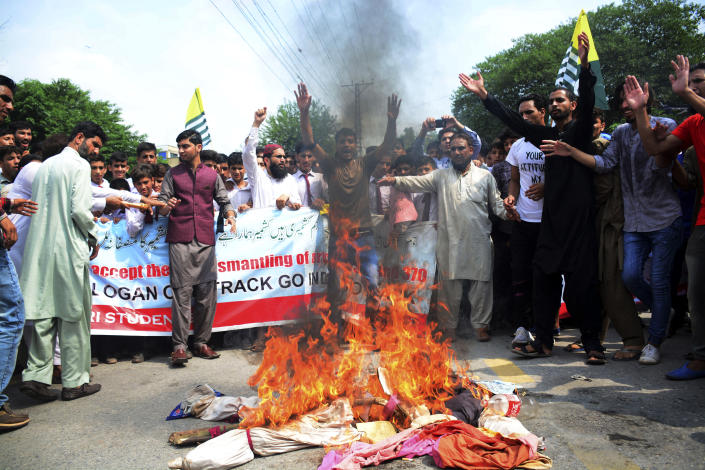 """Pakistani Kashmiris burn effigies of Indian leaders at a protest in Muzaffarabad, Pakistan, capital of Pakistani Kashmir, Friday, Aug. 9, 2019. Islamabad said it would downgrade its diplomatic ties with New Delhi, expel the Indian ambassador and suspend trade. Prime Minister Imran Khan told Pakistan's National Security Committee that his government will use all diplomatic channels """"to expose the brutal Indian racist regime"""" and human rights violations in Kashmir, the government's statement said. (AP Photo/M.D. Mughal)"""