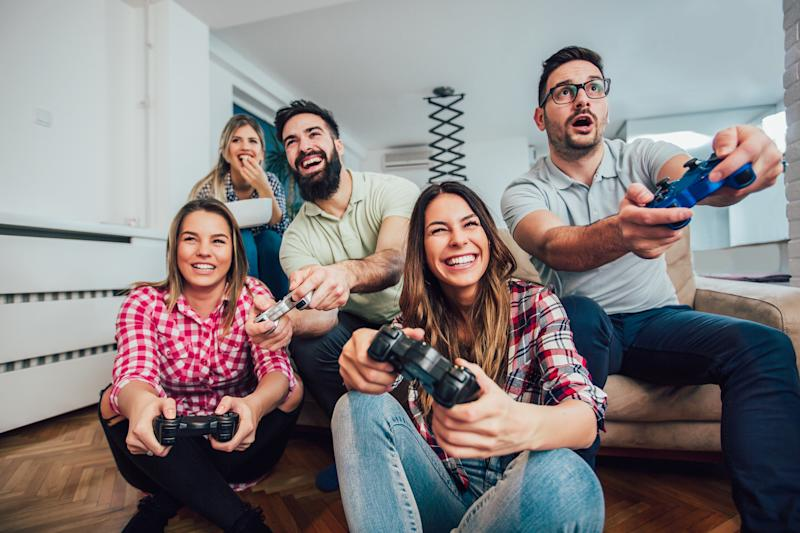 A group of friends play a video game in a living room.