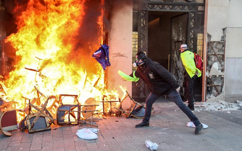 A Yellow Vest protester throws a flag of Europe towards a barricade burning in front of a shop on the Champs-Elysees avenue in Paris on March 16 - AFP