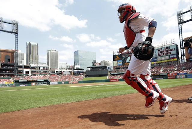 St. Louis Cardinals catcher Yadier Molina jogs onto the field at the start of a baseball game against the Pittsburgh Pirates on Thursday, Aug. 15, 2013, in St. Louis. Molina was activated Thursday after being on the 15-day disabled list with a right-knee sprain. (AP Photo/Jeff Roberson)
