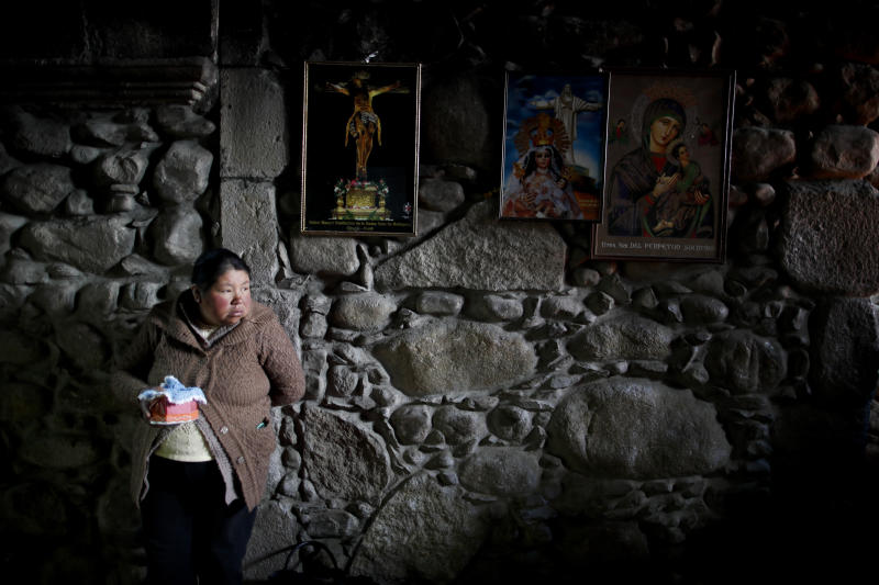 In this picture taken Jan. 6, 2020, a woman stands with her baby Jesus doll at San Francisco Church during the Three Kings Day celebrations in La Paz, Bolivia. Outside the church, many parishioners flocked to indigenous guides to get additional blessings, an ancestral tradition from the country's belief in the Pachamama, or mother earth deity. (AP Photo/Natacha Pisarenko)