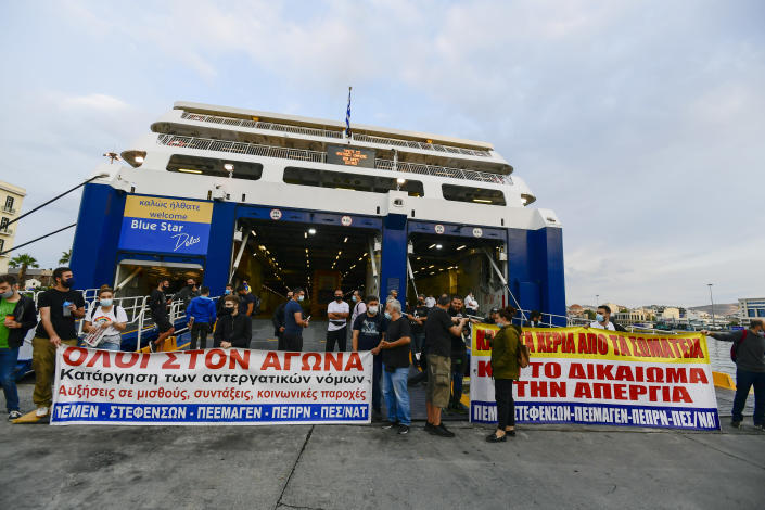 Protesters block the entrance of a passenger ferry during a 24-hour labour strike at the port of Piraeus, near Athens, Thursday, June 10, 2021. Greece's biggest labor unions stage a 24-hour strike to protest a draft labor bill being debated in parliament, which workers say will erode their rights. (AP Photo/Michael Varaklas)