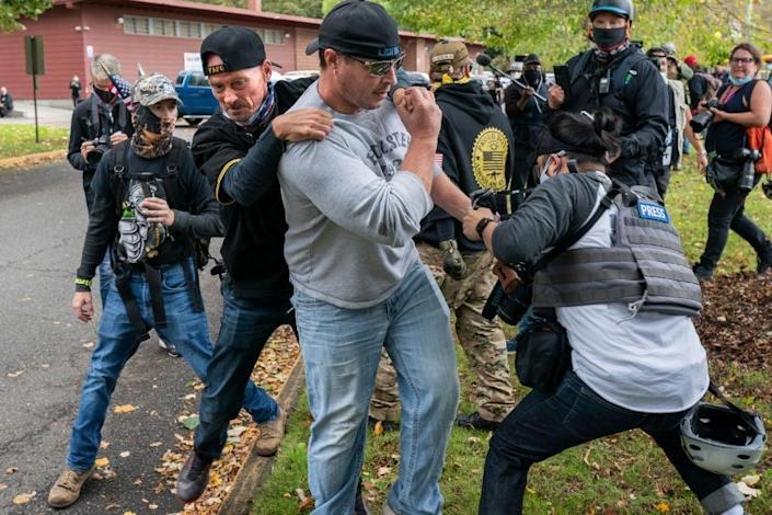 A Proud Boys member pulls away another who was assaulting a freelance journalist in Portland, Oregon, last week. (Getty Images)