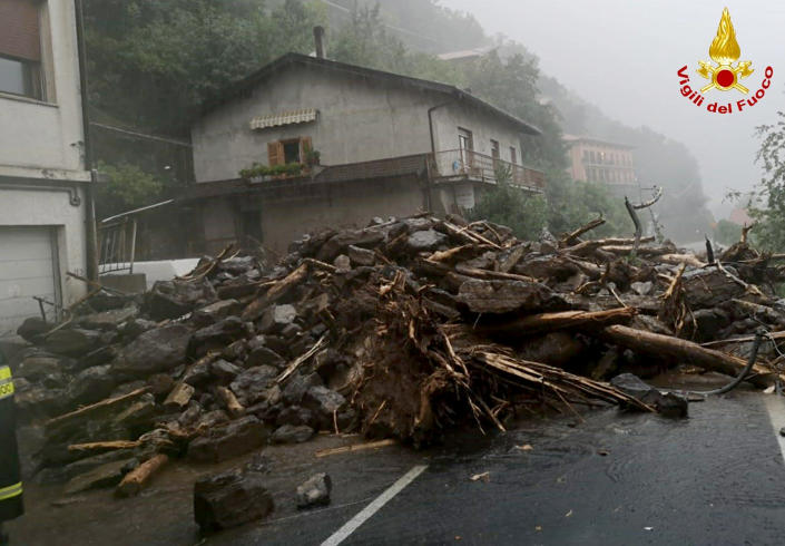 Branches and rocks lie on the asphalt after a landslide hit a road near Lake Como, Italy, Tuesday, July 27, 2021. Towns around Italy's Lake Como hit by mudslides and floods on Tuesday, in yet an extreme example of extreme weather phenomenon that an agricultural lobby said Tuesday has intensified in recent years. Italian firefighters carried out more than 60 rescues after storms wreaked havoc around the picturesque lake ringed by mountains in northern Italy. They included bringing to safety an elderly woman blocked in her home, as well as a person with a disability and a caregiver isolated by a landslide. No deaths or injuries were reported. (Vigili del Fuoco via AP)