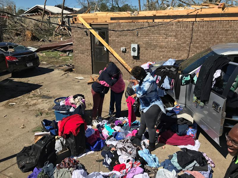 Naya Sanders, 12, left, and her mom, Gail Sanders, hug outside their home in Cairo, Georgia, as family friend Tasha Copeland wipes a tear from her eye. The Sanders lost their roof and their possessions when a tornado hit March 3.