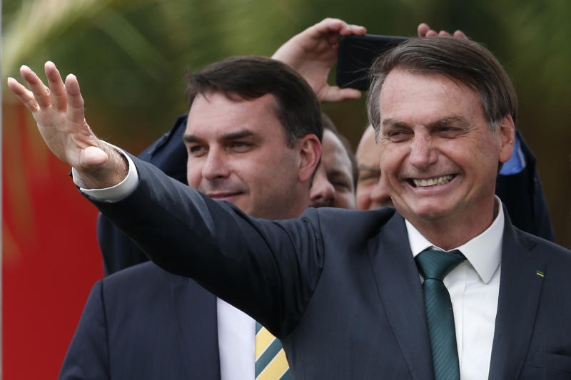 Accompanied by his son Sen. Flavio Bolsonaro, Brazil's President Jair Bolsonaro waves at the launch of his new political party, Alliance for Brazil, in Brasilia, Brazil, Thursday, Nov. 21, 2019. At odds with the party leadership that nominated him for the presidency, Bolsonaro left the Social Liberal Party earlier this month and created his own. (AP Photo/Eraldo Peres)
