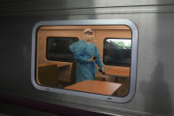 A health worker with protective gear walks inside a train as the train prepares to carry a group of COVID-19 patients to their hometowns, at Rangsit train station in Pathum Thani Province, Thailand, Tuesday, July 27, 2021. Thai authorities began transporting some people who have tested positive with the coronavirus from Bangkok to their hometowns on Tuesday for isolation and treatment, to alleviate the burden on the capital's overwhelmed medical system. (AP Photo/Sakchai Lalit)