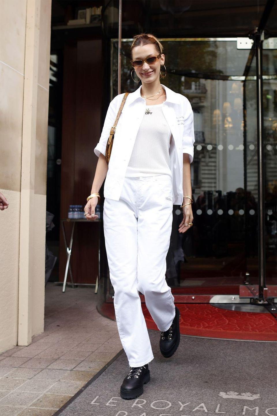 <p>In a white button-up, white tank, white trousers, black combat boots, layered gold necklaces, gold hoops, and brown shades.</p>