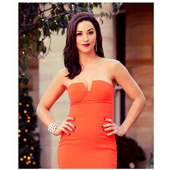A photo of The Bachelor Australia 2015 contestant Jacinda Gugliemino wearing an orange strapless dress on set.
