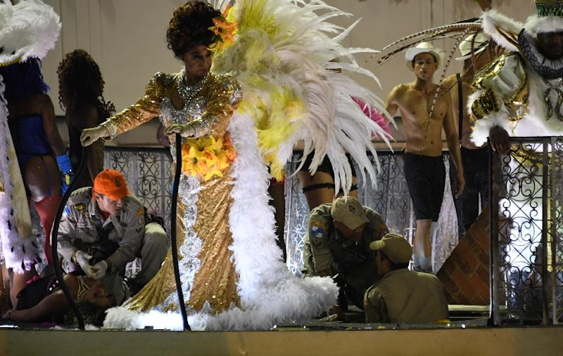 A firefighter (L) assists a reveller of the Unidos da Tijuca samba school at the Sambadrome in Rio de Janeiro, early on February 28, 2017, after the third floor of an allegorical car collapsed during the second night of Rio Carnival (AFP Photo/Vanderlei Almeida)
