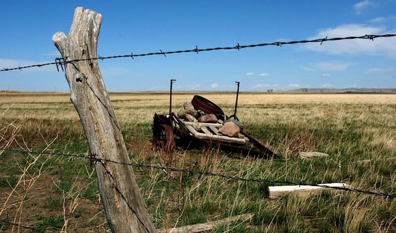A rusted piece of farm equipment is seen behind a barbed wire fence on ranchland north of the American Prairie Reserve south of Malta, Mont. in this April 25, 2012 photograph. The reserve on Monday closed a deal to buy a 150,000-acre ranch in nearby Valley County as part of a privately-funded effort to create three million-plus acres of wildlife habitat on the prairies of northcentral Montana. (AP Photo/Matt Brown)