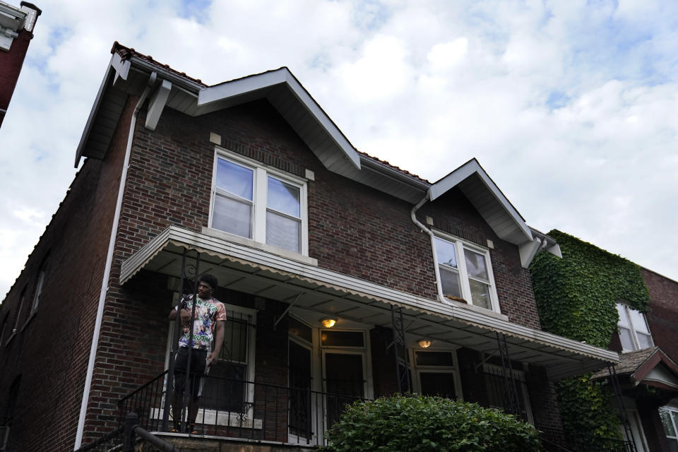 A man stands outside of the home of Craig Elazer in St. Louis on Friday, May 21, 2021. Elazer died from a fentanyl overdose. As the COVID-19 pandemic intensified America's opioid addiction crisis in nearly every corner of the country, many Black neighborhoods like this one suffered most acutely. (AP Photo/Brynn Anderson)