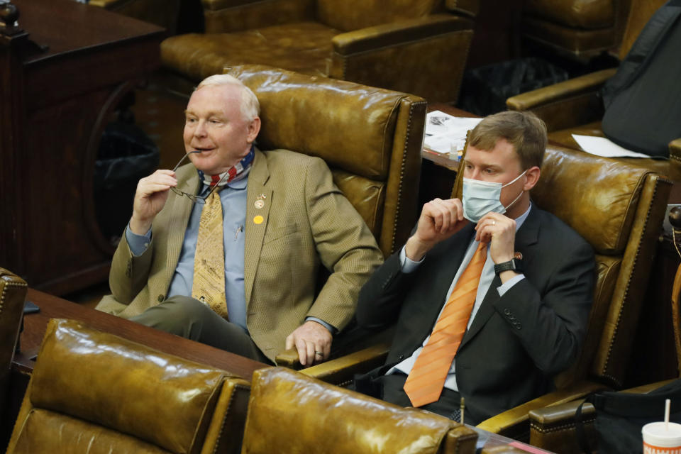 An unmasked Republican Rep. Dana Criswell of Olive Branch, left, sits alongside masked Republican colleague Joel Bomgar, of Madison, Monday, Aug. 10, 2020, as they listen to House Education Committee chairman Richard Beckett, unseen, explain the partial veto of the education budget bill in July by Gov. Tate Reeves, at the Capitol in Jackson, Miss. The House voted 109-7 to override Reeves's veto of the education bill, (AP Photo/Rogelio V. Solis)