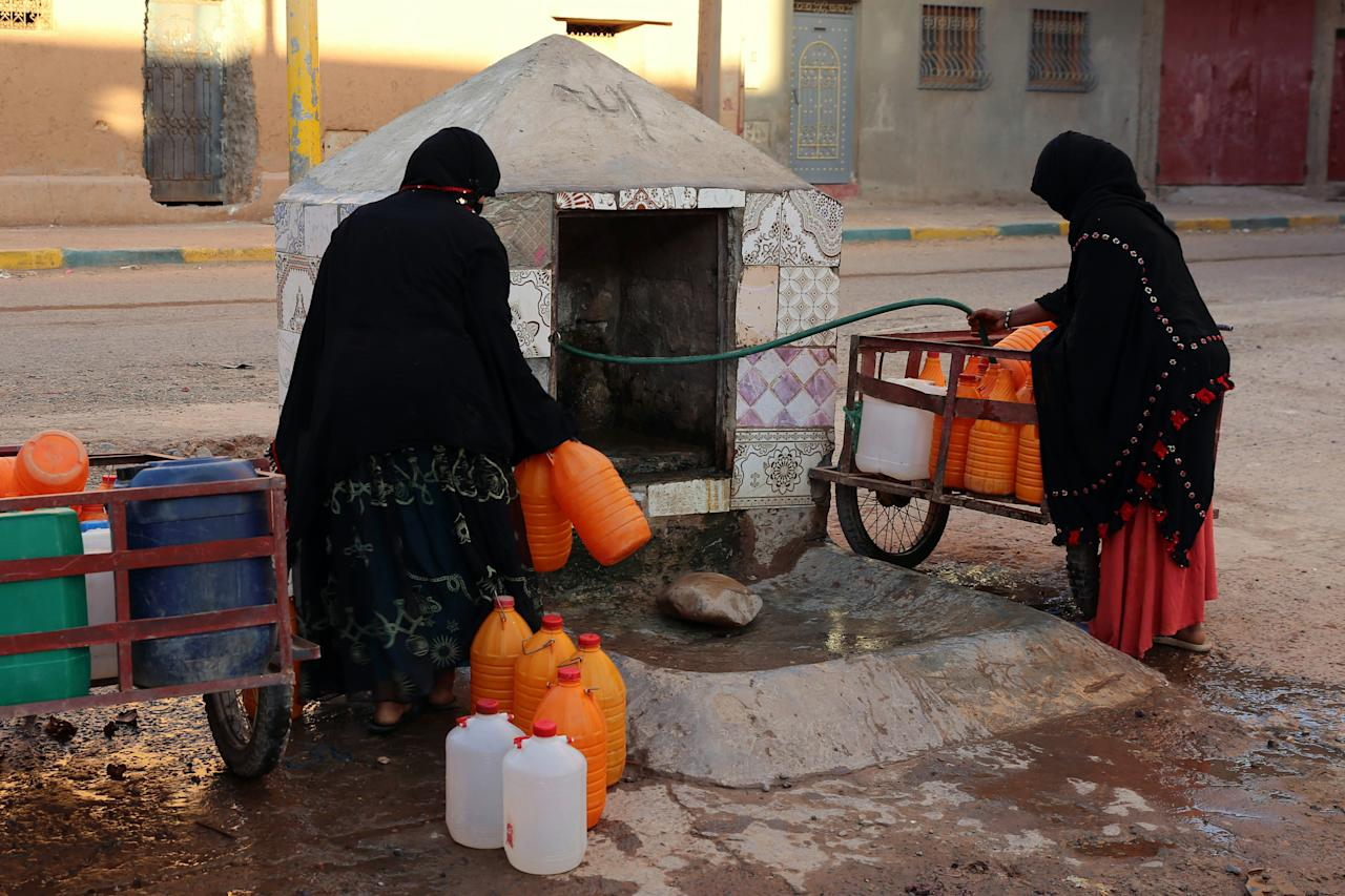 <p> FILE - A Thursday Oct. 19, 2017 file photo of Moroccan women filling up containers with water from a hose, in Zagora, southeastern Morocco. Experts blame poor choices in agriculture, growing populations and climate change for the water shortages in towns like Zagora, which has seen repeated protests for access to clean water in recent weeks. Moroccan state TV channel 2M reports that at least 15 people have died and 5 others have been injured in a stampede Sunday Nov. 19, 2017 as food aid was being distributed in the village of Sidi Boulalam, in the southern province of Essaouira. (AP Photo/Issam Oukhouya, File) </p>