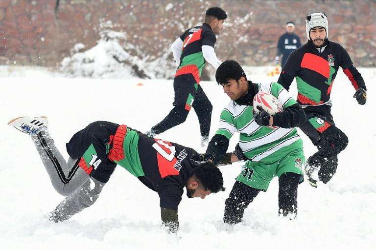 Afghan men enjoy a game of rugby in the snow in the capital, Kabul