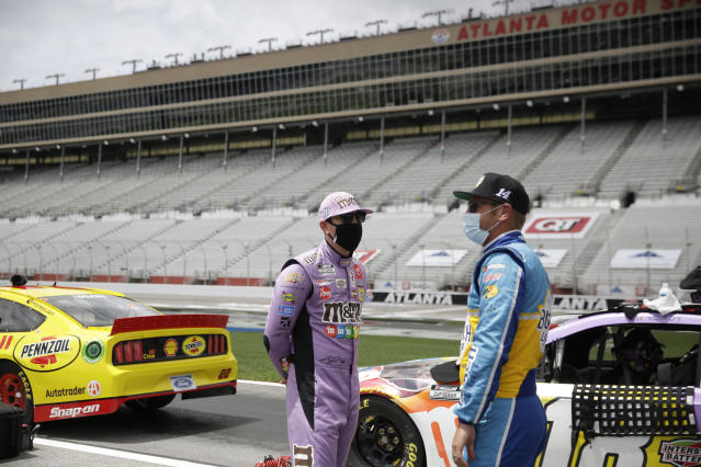 Kyle Busch (18) and Clint Bowyer (14) talk on pit row before a NASCAR Cup Series auto race at Atlanta Motor Speedway, Sunday, June 7, 2020, in Hampton, Ga. (AP Photo/Brynn Anderson)
