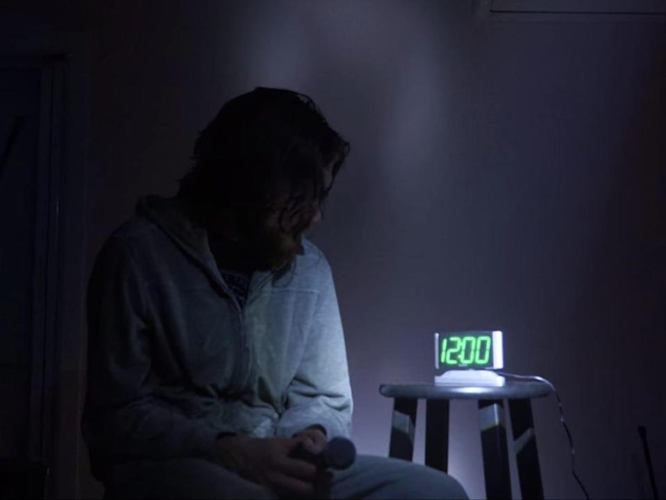 Bo Burnham sitting in a dark room watching a clock that's next to him on a stool.
