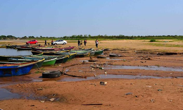 People walk next to boats along the exposed bed of a branch of the Paraguay river that has gone dry, in Lambare, Paraguay, on 17 September.