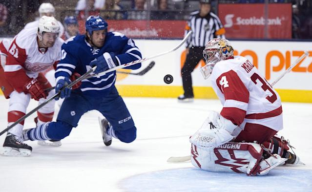 Detroit Red Wings goaltender Petr Mrazek, right, makes a save as Wings' Jeff Hoggan (81) tries to control Toronto Maple Leafs' Troy Bodie during second-period preseason NHL hockey game action in Toronto, Saturday Sept. 28, 2013. (AP Photo/The Canadian Press, Frank Gunn)