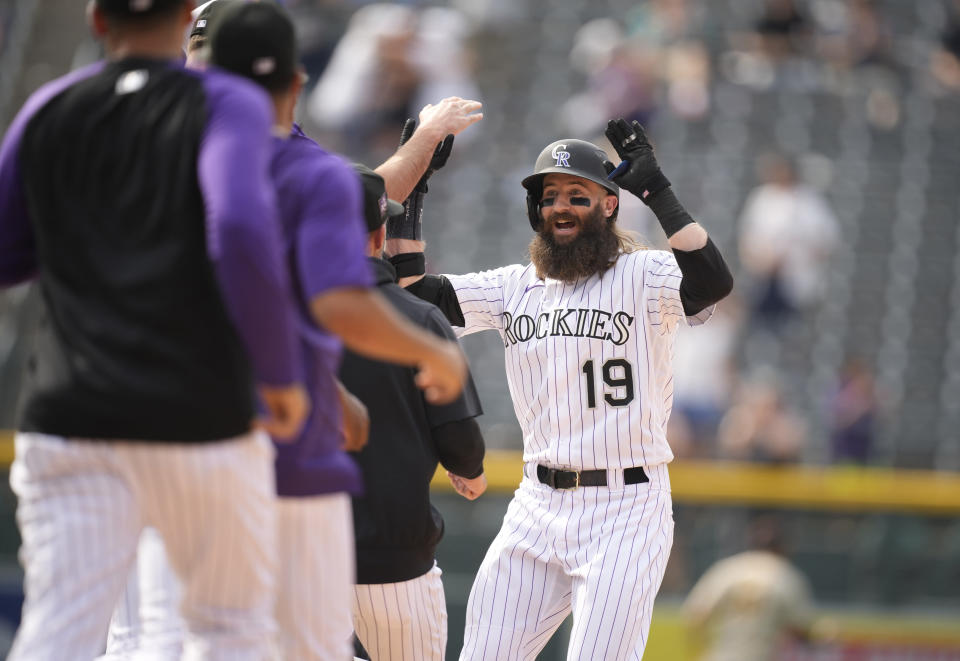 Teammates run to Colorado Rockies pinch-hitter Charlie Blackmon, right, to celebrate after his walkoff, RBI-single off San Diego Padres relief pitcher Austin Adams in the ninth inning of a baseball game Wednesday, June 16, 2021, in Denver. The Rockies won 8-7 to sweep the three-game set. (AP Photo/David Zalubowski)