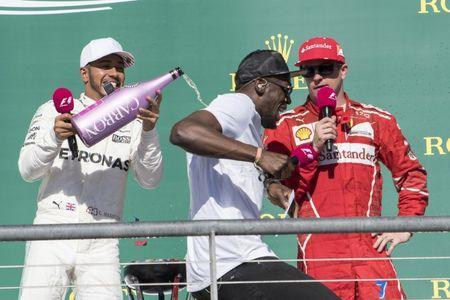 Oct 22, 2017; Austin, TX, USA; Mercedes driver Lewis Hamilton (44) of Great Britain pours champagne down the back of Olympic champion Usain Bolt after Hamilton wins the United States Grand Prix at Circuit of the Americas. Mandatory Credit: Jerome Miron-USA TODAY Sports