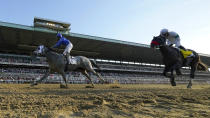 Jockey Luis Saez reacts after crossing the finish line ahead of Hot Rod Charlie (4), with jockey Flavien Prat up, to win the 153rd running of the Belmont Stakes horse race with Essential Quality (2),, Saturday, June 5, 2021, At Belmont Park in Elmont, N.Y. (AP Photo/Seth Wenig)
