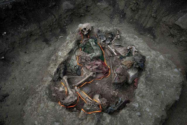 <p>An orange ribbon outlines skeletal remains in a mass grave unearthed in the village Paccha of Peru on Sept. 8, 2014. For three decades, the soil of this unpopulated hamlet on the Andean slopes beside the Apurimac river guarded bodies of villagers slain by security forces who considered them adherents of the Shining Path rebels. (AP Photo/Rodrigo Abd) </p>