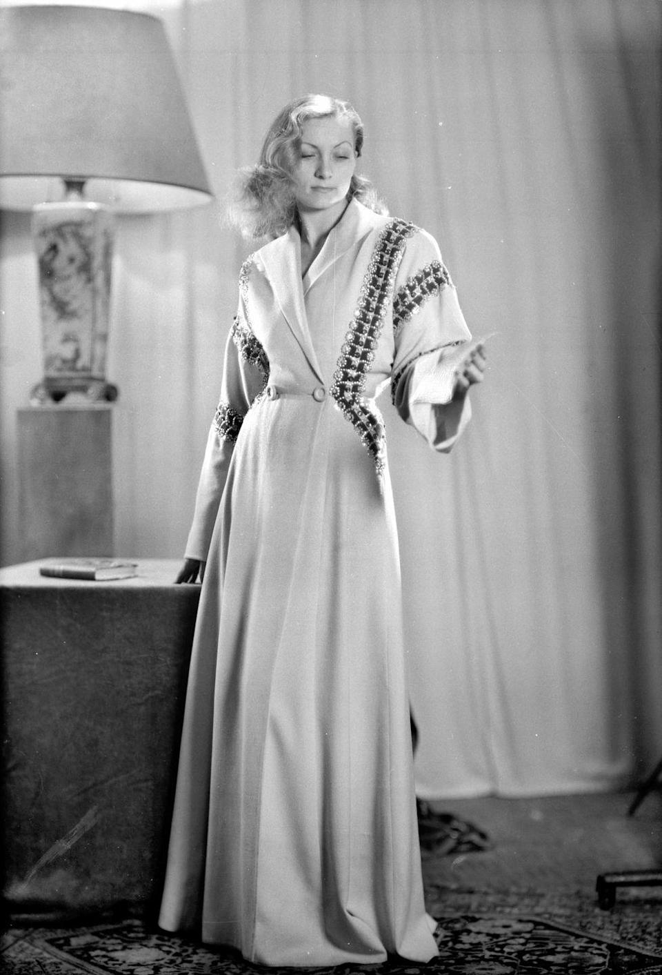<p>A model reads a piece of paper as she wears a housecoat designed by Jeanne Lanvin.</p>