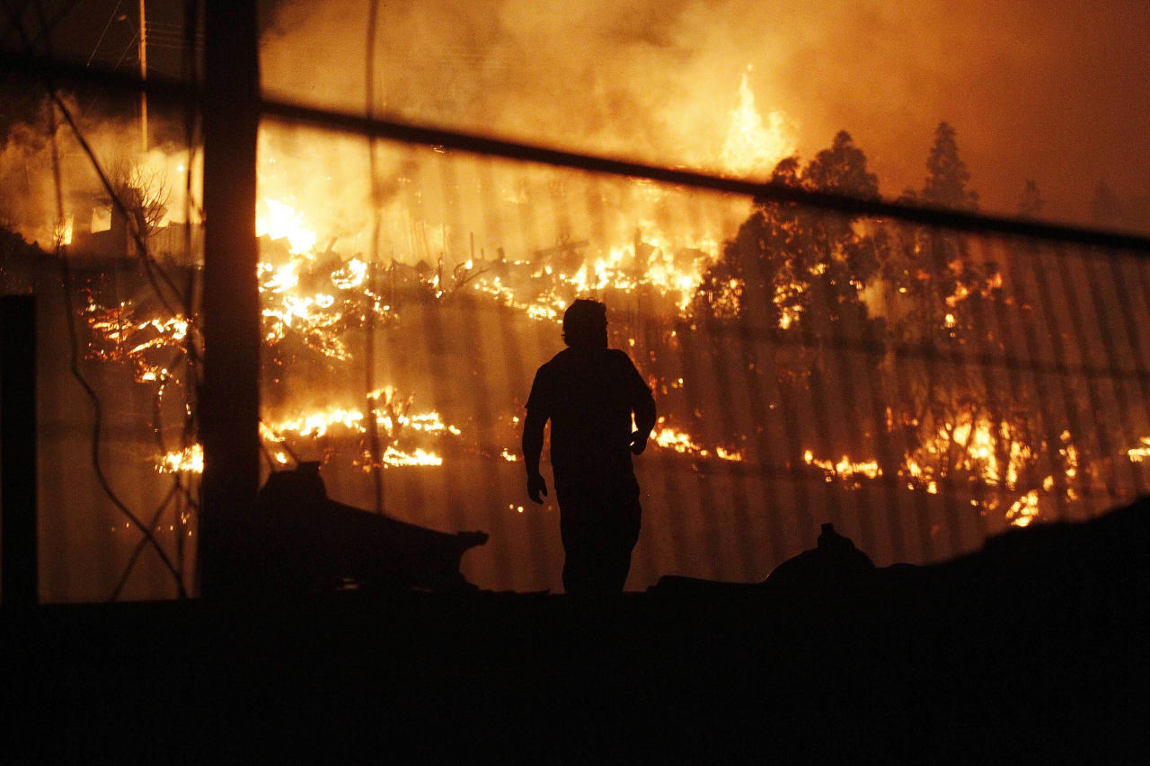 A man walks as an out of control forest fire destroys homes in the city of Valparaiso, Chile, Sunday April 13, 2014. Firefighters struggled for a second night to contain blazes that reached this port city, killing at least a dozen people, destroyed hundreds homes and has forced the evacuation of thousands. (AP Photo/Luis Hidalgo)