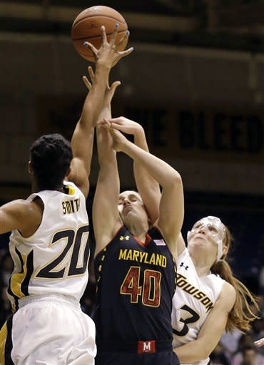 Maryland guard Katie Rutan (40) is fouled as she goes up for a shot between Towson forward Markell Smith, left, and guard Ciara Webb during the first half of an NCAA college basketball game in Towson, Md., Tuesday, Dec. 11, 2012. (AP Photo/Patrick Semansky)