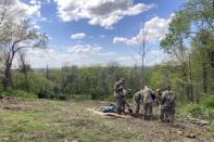 Members of the Ohio National Guard plant one of the trees at the dedication of Ohio's COVID-19 Pandemic Memorial Grove at Great Seal State Park near Chillicothe, Ohio., April 30, 2021. The country has begun finding ways to remember the more than 600,000 Americans who have died from the coronavirus, but the process is fraught compared to past memorial drives because of the politics. (AP Photo/Julie Carr Smyth)