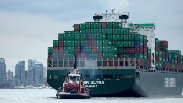 A Port of Vancouver tug guides a large container ship clear of the loading area. According to the director at the Burnaby Board of Trade, container shipping costs have increased more than 400 per cent since January 2021. (David Horemans / CBC - image credit)