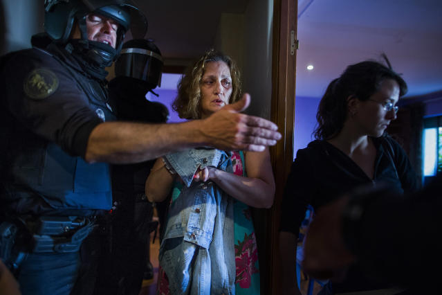 <p>Carmen Rives, 50, gestures as riot police enter her apartment to evict her, Madrid, June 2, 2015. (AP Photo/Andres Kudacki) </p>