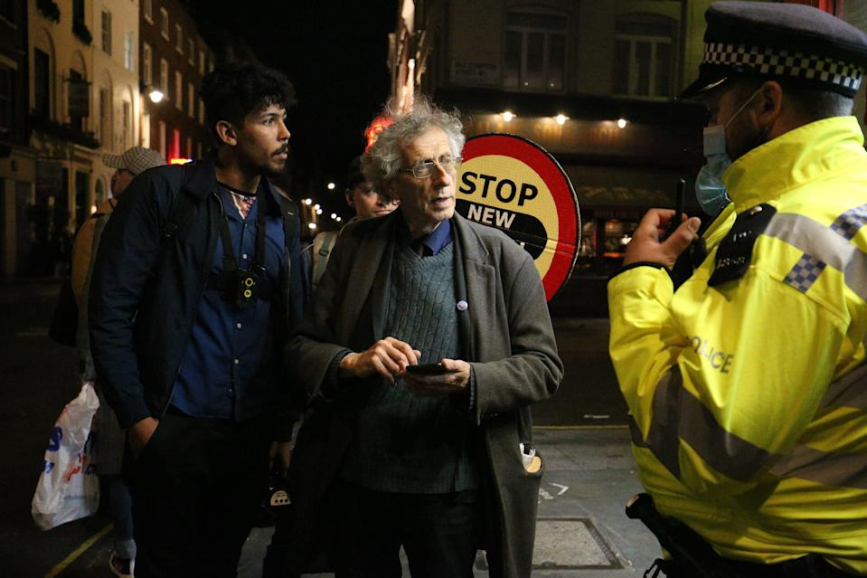 Police chat with Piers Corbyn in Soho on Friday night (PA)