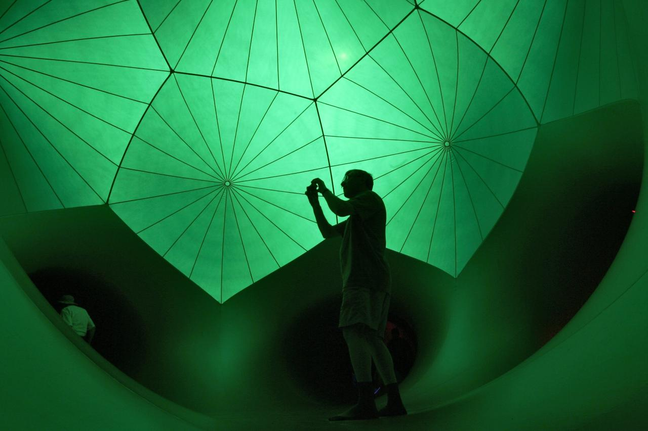 A man takes a photograph inside Exxopolis, an inflatable walk-in luminarium at Grand Park in Los Angeles, California, September 7, 2013. The inflatable walk-in luminarium, designed by Architects of Air, creates a maze of winding paths and domes featuring Islamic architecture, Archimedean solids, and Gothic cathedral designs. REUTERS/Jonathan Alcorn (UNITED STATES - Tags: SOCIETY TPX IMAGES OF THE DAY)
