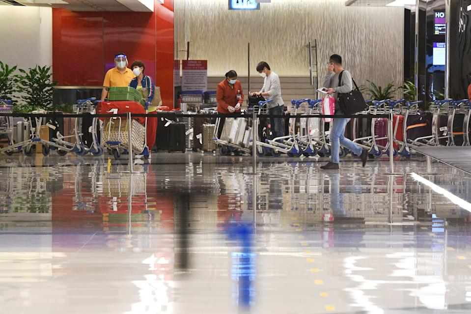 Travellers collect their luggage at the arrival hall after landing at Singapore Changi Airport in Singapore.