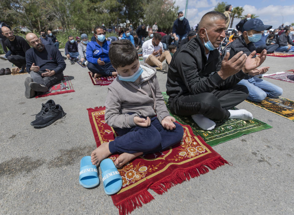 Palestinians practice outdoor social distancing while attending the last Friday prayers ahead of the upcoming Muslim fasting month of Ramadan, at a parking lot in the West Bank city of Ramallah, Friday, April 9, 2021. The West Bank welcomes Ramadan this year while under lockdown measures, due to a surge in COVID-19 cases, that includes restrictions on mosques indoor mass prayers. (AP Photo/Nasser Nasser)