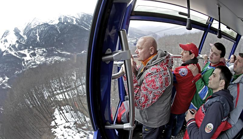 Fans watch the view from a gondola as the head to a cross-country sprint race at the 2014 Winter Olympics, Tuesday, Feb. 11, 2014, in Krasnaya Polyana, Russia. (AP Photo/Charlie Riedel)