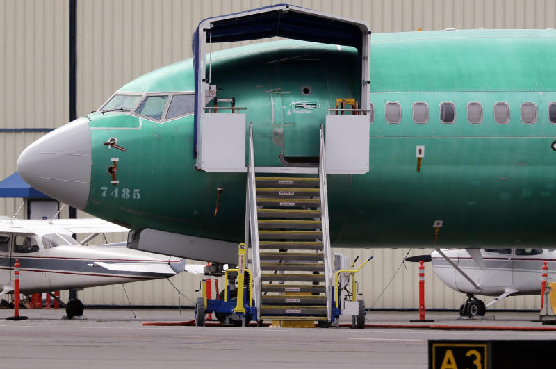 FILE - In this April 8, 2019, file photo a Boeing 737 MAX 7 jet is parked near single engine planes at the airport adjacent to a Boeing Co. production facility in Renton, Wash. Federal safety officials say Boeing should consider how cockpit confusion can slow the response of pilots who are dealing with the kind of problem that likely caused two airliners to crash in the past year. (AP Photo/Elaine Thompson, File)