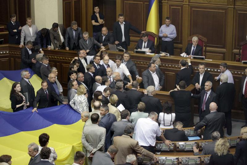 Lawmakers surround the tribune in Ukraine's parliament in Kiev, Ukraine,Tuesday, June 5, 2012. Several thousand flag-waving activists staged a noisy protest outside the parliament building, protesting the bill that would keep Ukrainian as the only official language in the country, but Russian could be used in courts, hospitals and other institutions in Russian-speaking regions. Defying vehement opposition, Ukraine's pro-government lawmakers on Tuesday gave tentative approval to a hotly contested bill that would allow the use of the Russian language alongside Ukrainian in some regions. (AP Photo/Efrem Lukatsky)
