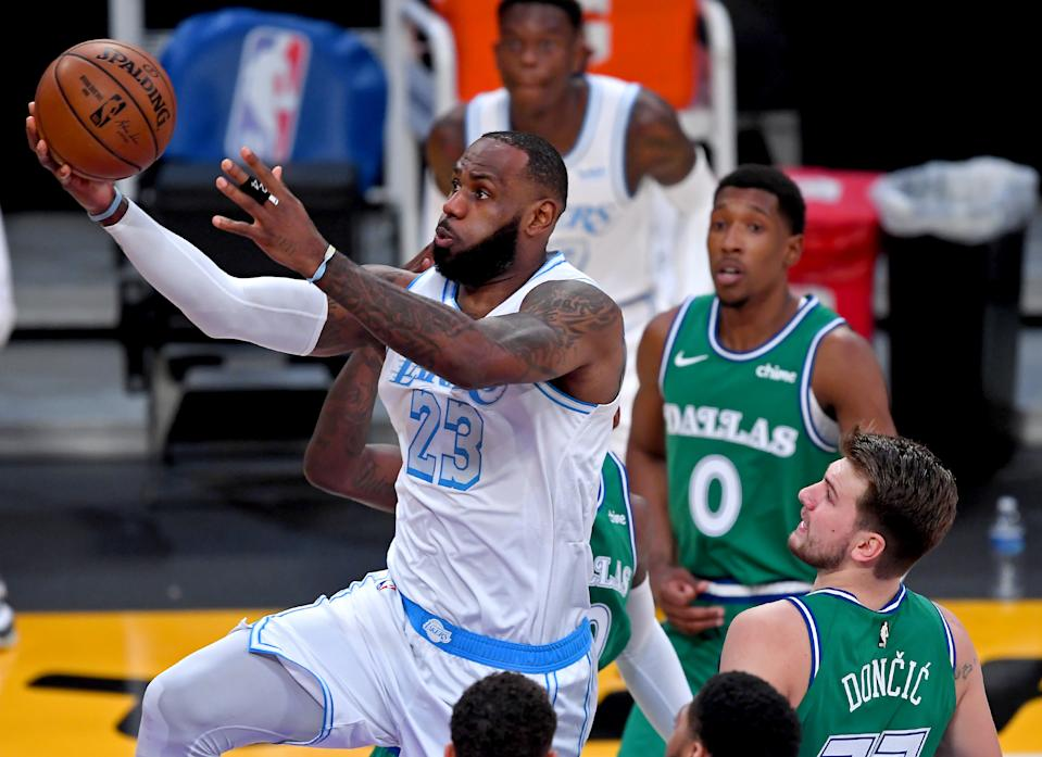 Dec 25, 2020; Los Angeles, California, USA;  Los Angeles Lakers forward LeBron James (23) drives past Dallas Mavericks forward Dorian Finney-Smith (10) and Dallas Mavericks guard Luka Doncic (77) for a basket in the first quarter of the game at Staples Center. Mandatory Credit: Jayne Kamin-Oncea-USA TODAY Sports