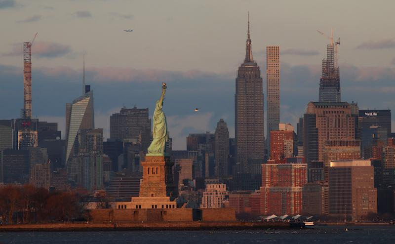 BAYONNE, NJ - DEC 15: The Statue of Liberty stands in front of buildings across midtown Manhattan, the Steinway Tower, Bank of America Building, Rockefeller Center, the Empire State Building, 432 Park Avenue, One Vanderbilt and the MetLife Building as the sun sets in New York City on December 15, 2019 as seen from Bayonne, New Jersey. (Photo by Gary Hershorn/Getty Images)