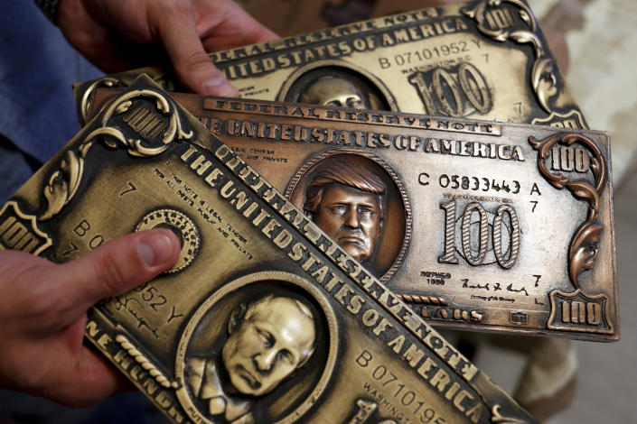 <p>Russian hacker Sergey Pavlovich, better known by his former online alias Police Dog, holds a mock money printing plate with Russian President Vladimir Putin, bottom, and US President Donald Trump, center, faces in place of Benjamin Franklin during an interview with the Associated Press in Moscow, Russia, Aug. 9, 2017. (Photo: Pavel Golovkin/AP) </p>