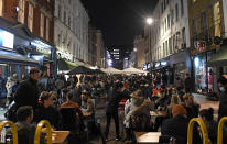 People dine and take drinks on Old Compton Street in the Soho area of central London, Saturday, Oct. 31, 2020. Earlier Saturday British Prime Minister Boris Johnson announced England will start a month long lockdown next week. Johnson says the new measures will begin Thursday and last until Dec. 2. (AP Photo/Alberto Pezzali, Pool)