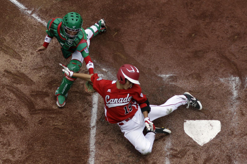 Vancouver, British Columbia's Thomas Neal, right, scores past Nuevo Laredo, Mexico's Marcelo Perez on a two-run double by Cortez D'Alessandro in the first inning of a pool play baseball game at the Little League World Series, Friday, Aug. 17, 2012, in South Williamsport, Pa. Canada won 13-9. (AP Photo/Matt Slocum)