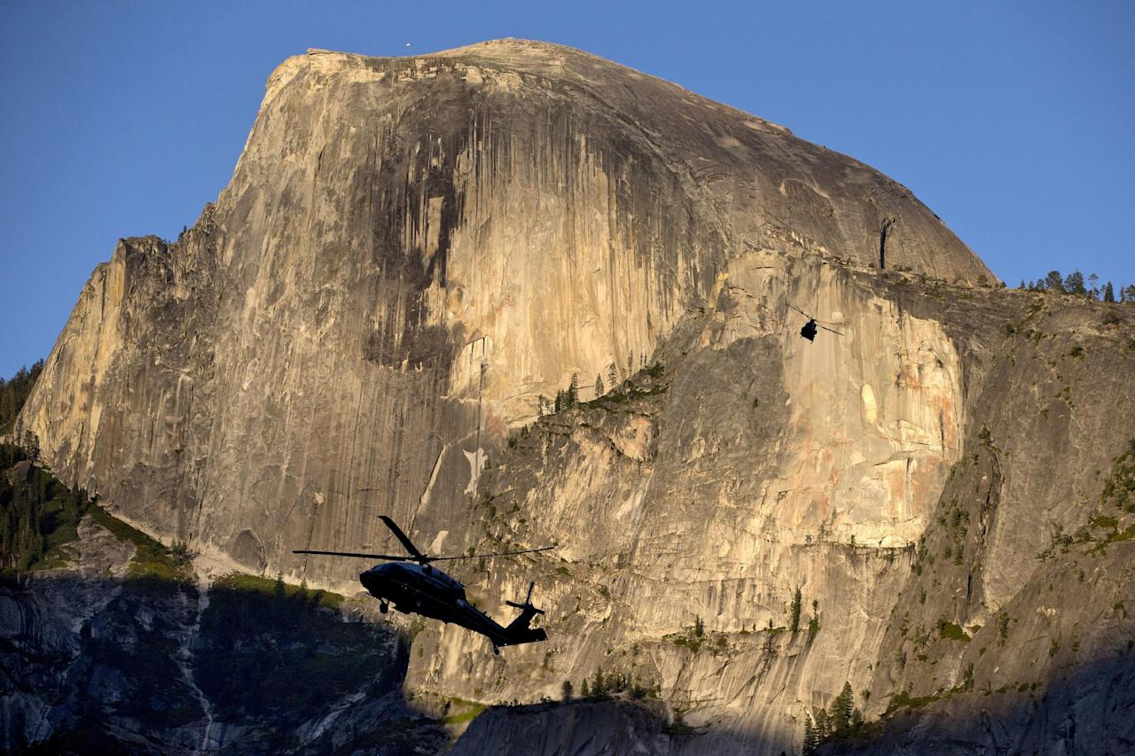 The Marine One helicopter carrying President Barack Obama, first lady Michelle Obama, and daughters Malia Obama and Sasha Obama, and a support helicopter are silhouetted against the Half Done rock formation at sunset as the first family arrives at Yosemite National Park, in Calif., Friday, June 17, 2016. The Obama family traveled to Carlsbad Caverns National Park in New Mexico before heading to Yosemite to celebrate the 100th anniversary of the creation of America's national park system. (AP Photo/Jacquelyn Martin)